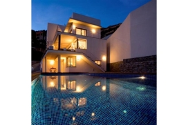 Wow factor, architect-designed luxury modern holiday villa with WIFI in Javea for up to 10 people, on the Costa Blanca, Spain. Located in the port area of Javea, 5 bedroom Villa La Corona is an easy walk down the hill to the restaurants and bars the port has to offer as well as the local fiestas and the spectacular fireworks displays in June and September. Also there is the Yacht Club, the pebble beach, shops and fashionable beach cafés.Apart from the great location, internally Villa Corona does not fail to impress. On 3 levels, the main level has a double bedroom and shower room, beautiful lounge-diner, superb fully equipped kitchen and adjoining covered terrace for outdoor eating and chilling out, where you can enjoy a cool drink at sunsetUpstairs are 2 double bedrooms, master suite with shower room and a further guest bathroom.At the pool level is the 5th bedroom and ensuite shower room as well as a huge playroom with a sofa, TV, treadmill and cross trainer. Glass doors lead out to the covered terrace with comfy sofas where you can sit in shade while keeping an eye on the children in the pool.All the bedrooms are air-conditioned.The private pool terrace is ideal for some serious sunbathing followed by a dip in the pool. 10 minutes by car takes you to the Arenal sandy beach area with restaurants, shops, bars and nightlife., Javea